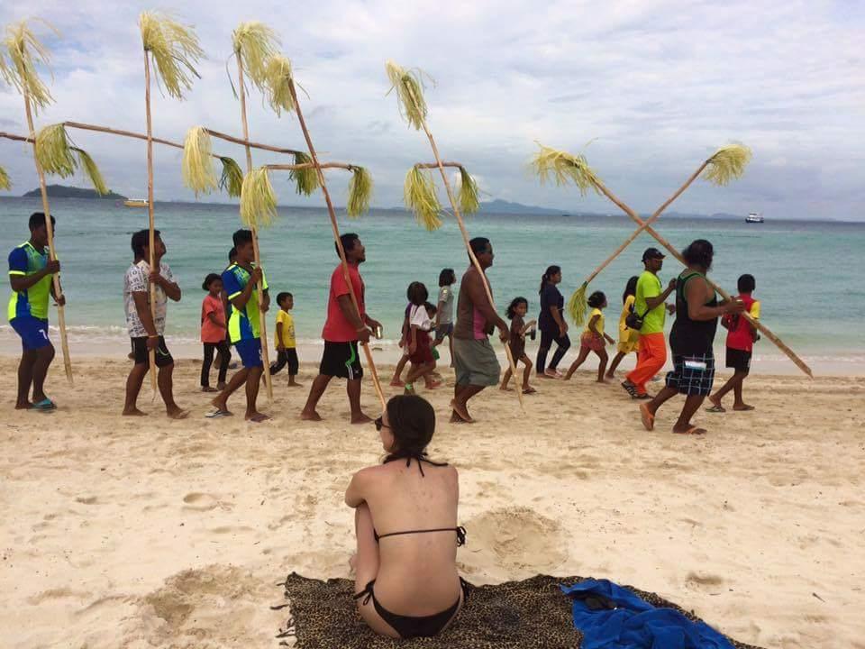 ชาวเลแหลมตง บนเกาะพีพี จังหวัดกระบี่ กำลังร่วมกันจัดงานลอยเรือ ขณะที่นักท่องเที่ยวต่างชาติจ้องมองอย่างสนใจ /ขอบคุณภาพโดย Wichot Kraithep
